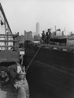 Photograph, Dockworkers Nosing Barge up to Pier, circa 1927 by Percy Loomis Sperr