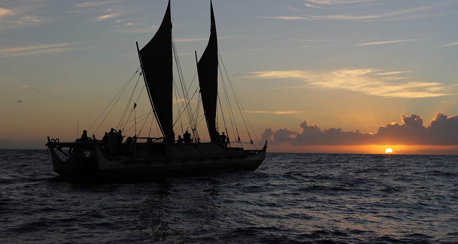 Hokule'a on the ocean at sunset